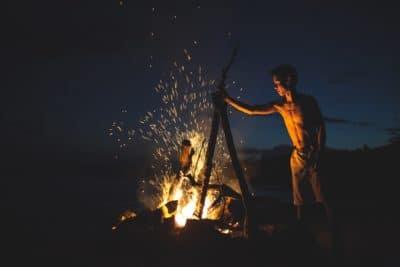 Topless man beside a fire.
