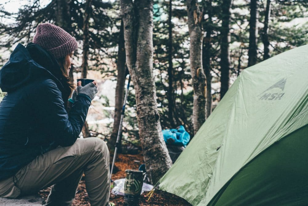 A woman sitting by a green tent in the forest drinking coffee.