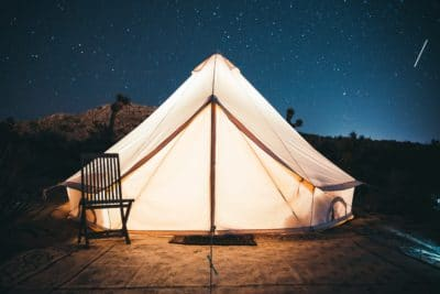 A white glowing cancas tent outside under the stars.