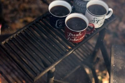 Four ceramic coffee mugs on a grill outside.