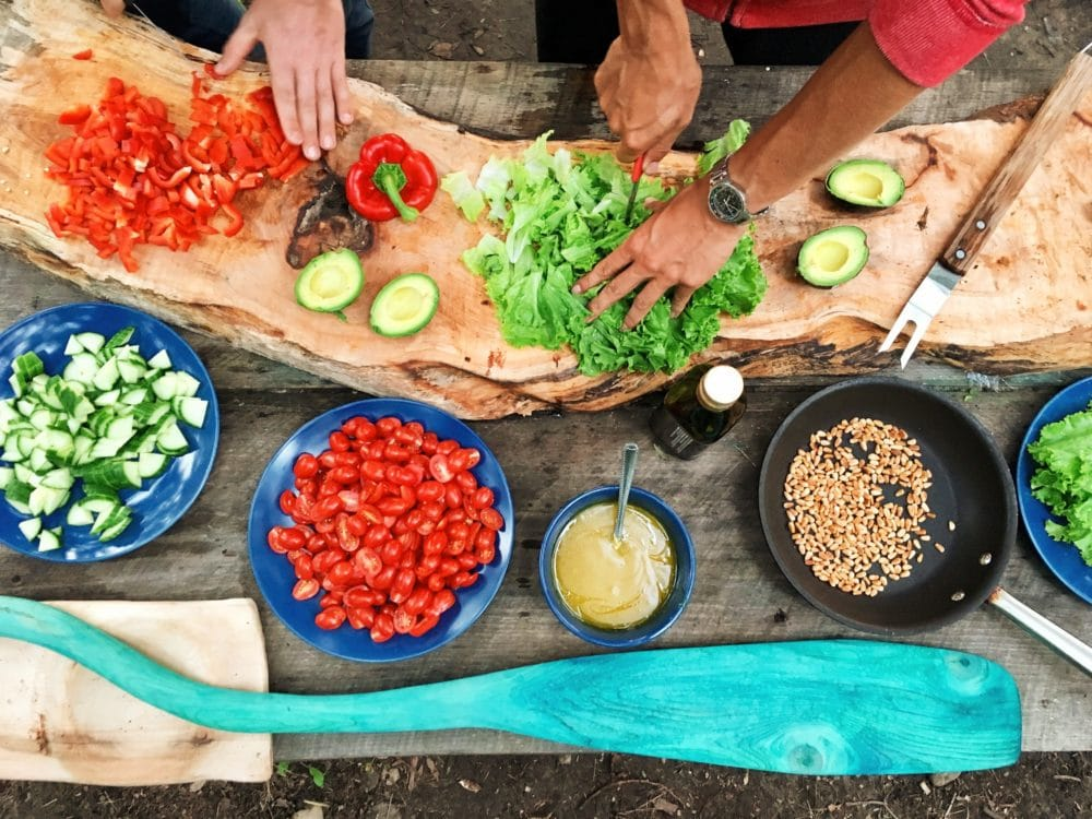 People cutting up an assortment of vegetables.