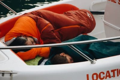A man and a young boy sleeping in sleeping bags on a boat.