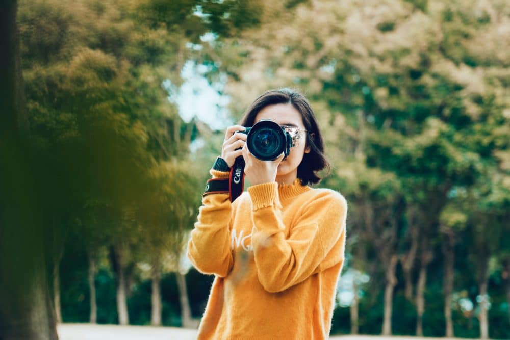 A girl in an orange sweater holding a camera.