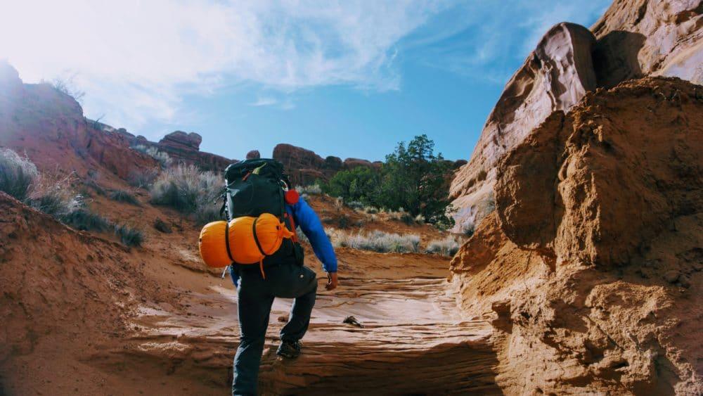 A hiker going through a rocky trail.