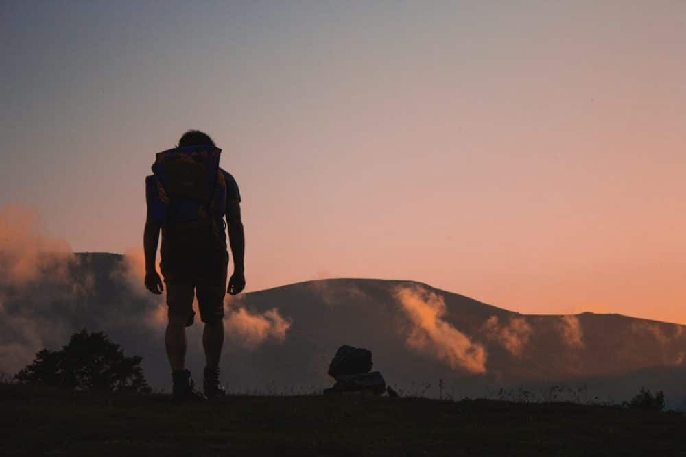 A hiker on a mountain during sunset.