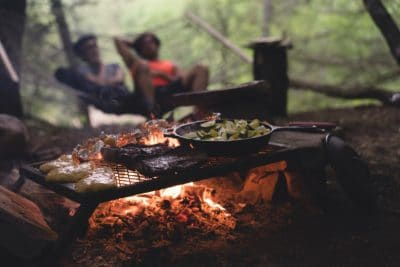 Some food cooking over a fire and people camping.