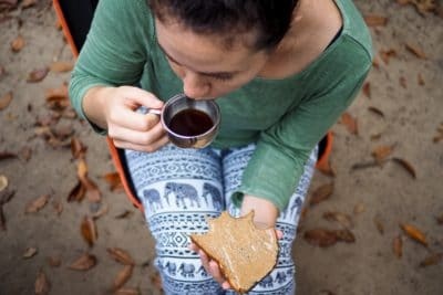 A woman drinking coffee and eating peanut butter on toast.