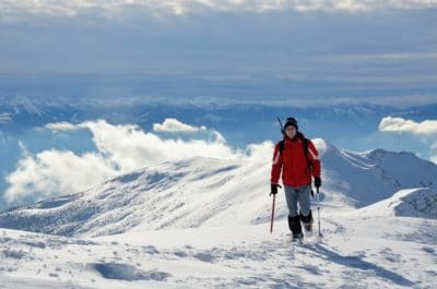 A skier in a red jacked in the snowy mountains.