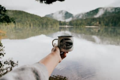 A person holding a coffee mug by a lake.