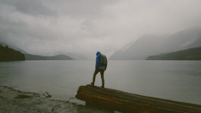A man standing on a wooden plate by a like in the rain.