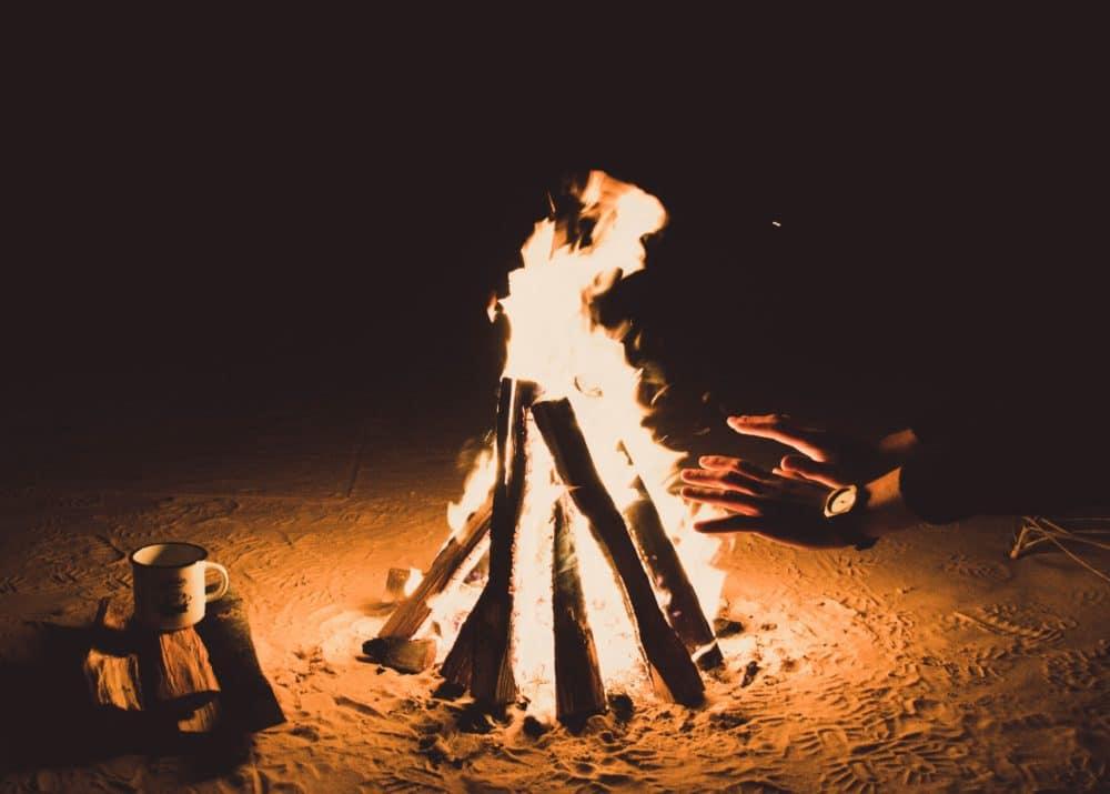 Person heating hands beside fire.