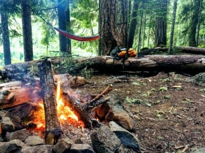 A campsite with a fire and a hammock.