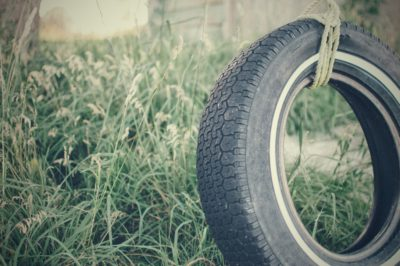 A tire swing in the grass.