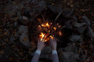 A person warming their hands by a fire.