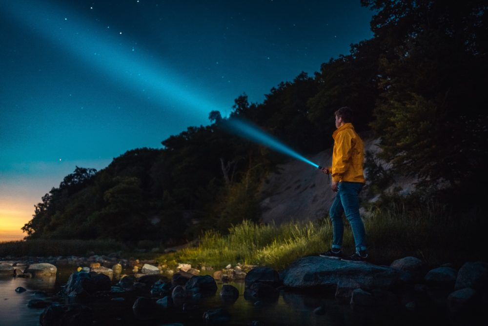 Man holding a flashlight in the woods at night.