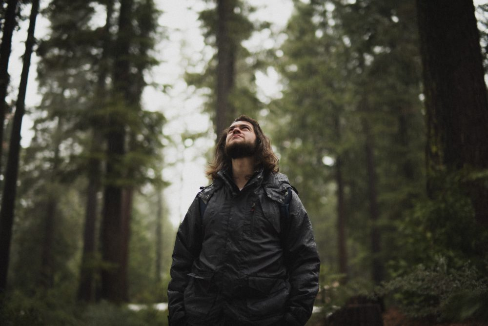 A man with a rain jacket in the forest in the rain.