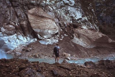 A man standing infant of a rock wall and river.