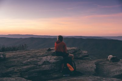 A man sitting on a rock ledge during sunset.