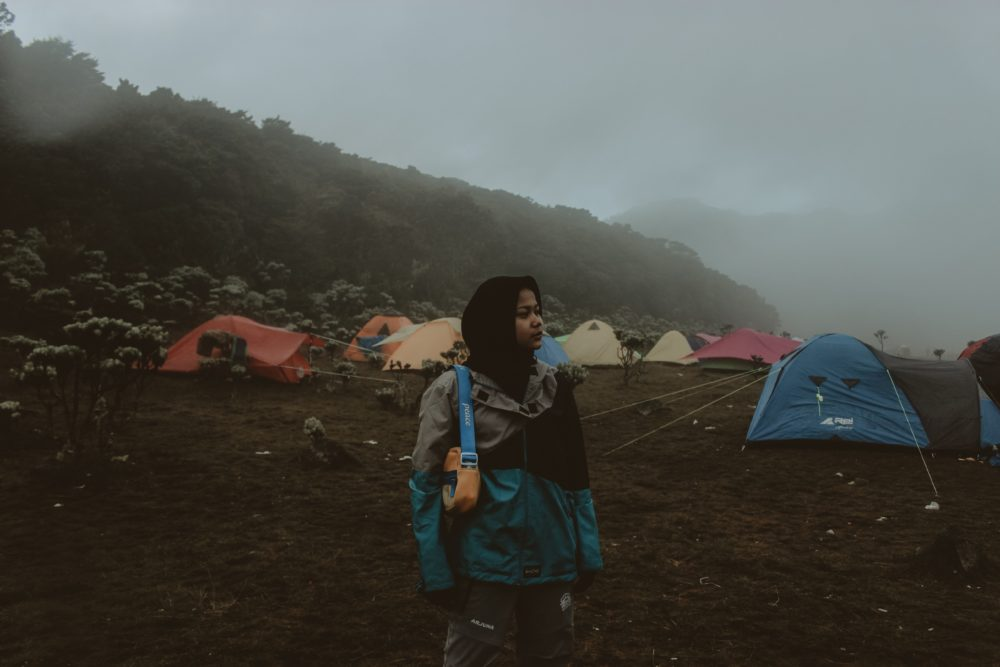 A woman standing in the fog at a campsite.