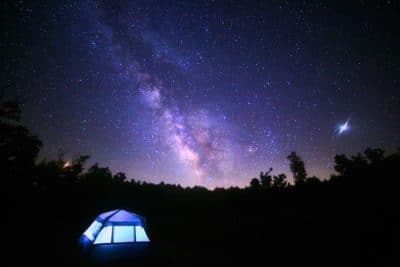 A blue tent under the stars at night.