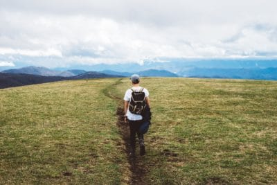 A man walking through a field in the mountains.