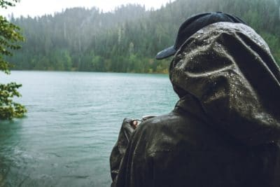 A person with a rain jacket in the rain by a lake.