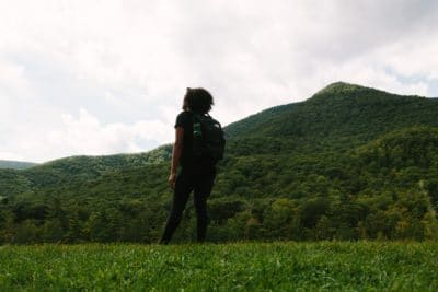 A backpacker by a green mountain.