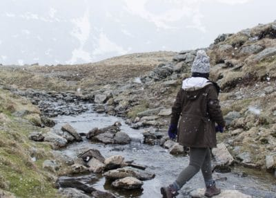 A girl walking over a stream in the mountains.