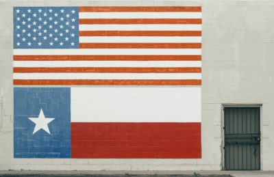 An American flag and Texas flag painted on wall.