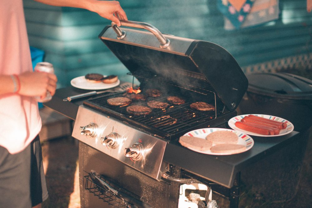 A person by a grill with burgers on it.