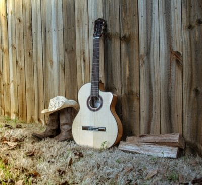 A classical guitar and a wooden fence.
