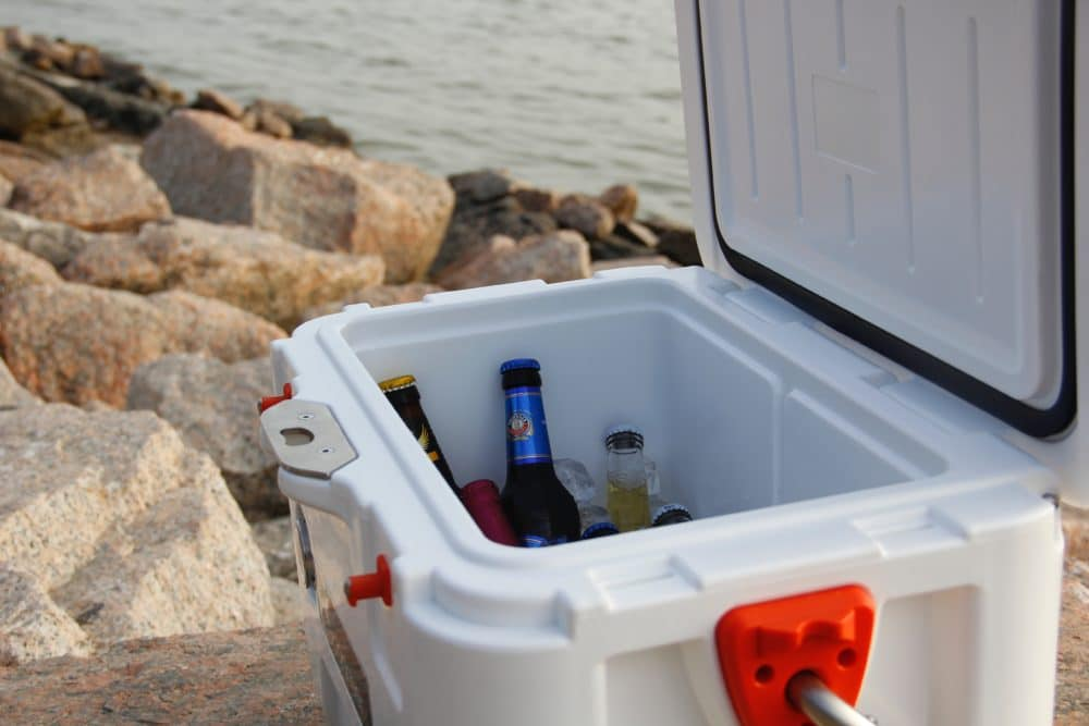 Drinks inside a white cooler by water.