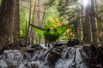 Two person sitting in a green hammock over a creek in the woods.