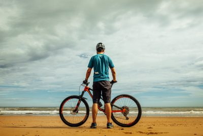 A man with this bike on the beach.
