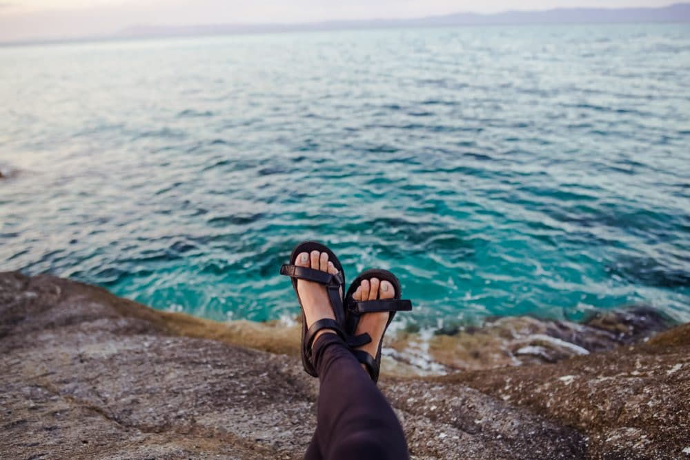 A person with sandals by the sea.