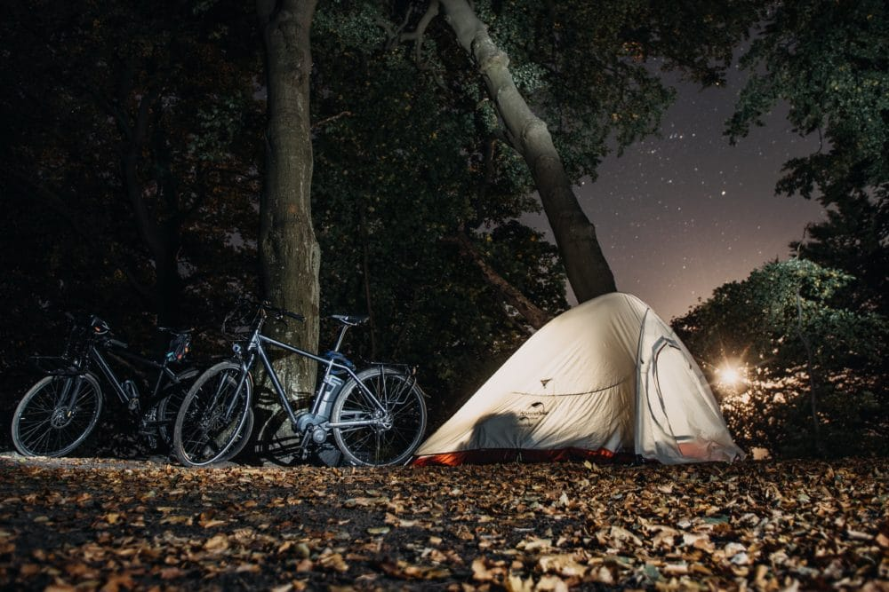 A tent and some bikes in the forest at night.