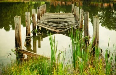 Brown wooden dock surrounded by water.