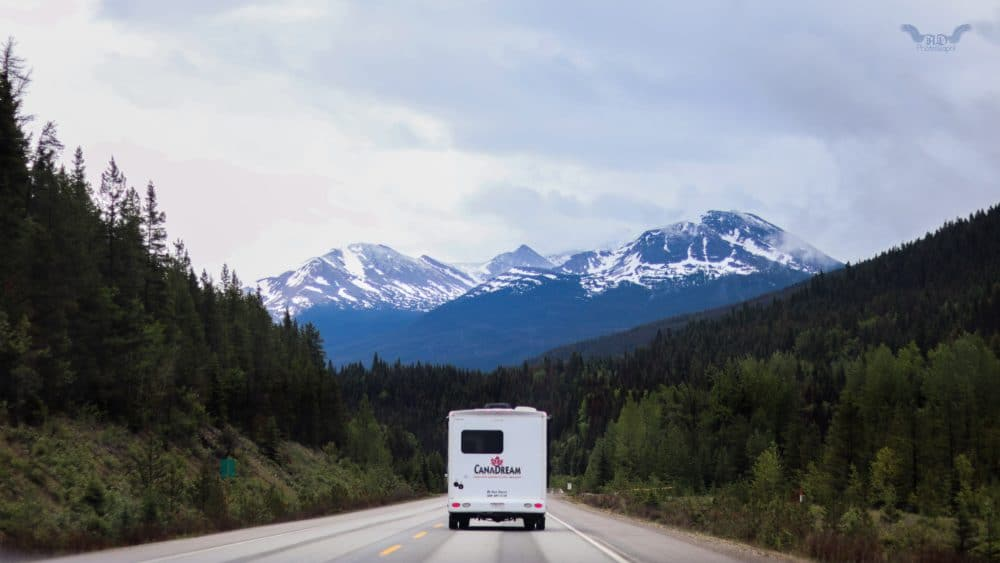 white RV driving down a road in the mountains.