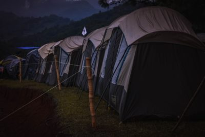 A row of canvas tents in the dark.