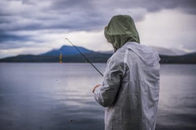 A man fishing by the lake on a cloudy day.