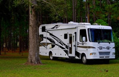 A white RV on the grass.