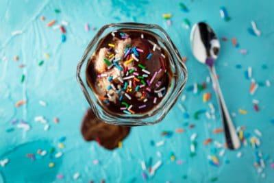 An ice cream sundae with sprinkles on a blue table.