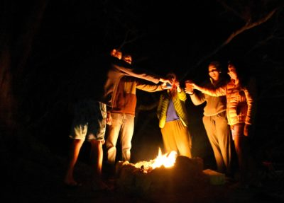 People standing around a campfire at night.