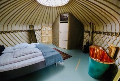 Inside of a tent with a bed.