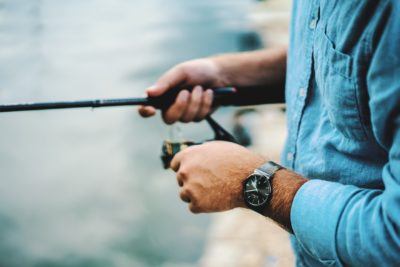 A person holding a fishing rod by a lake.