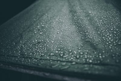 A green tarp with rain droplets on it.