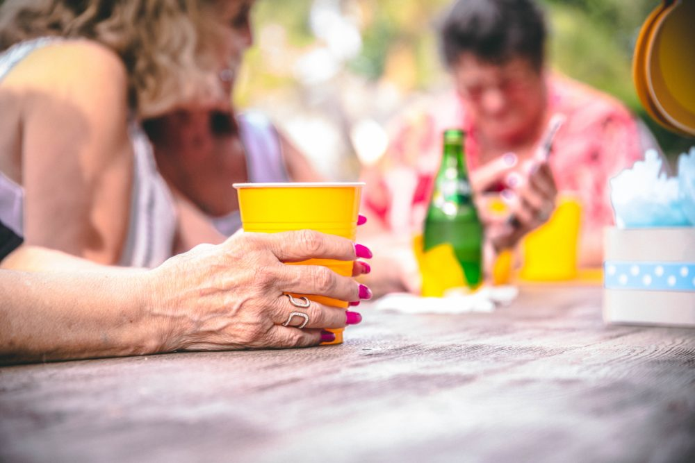 People drinking outside around a table.