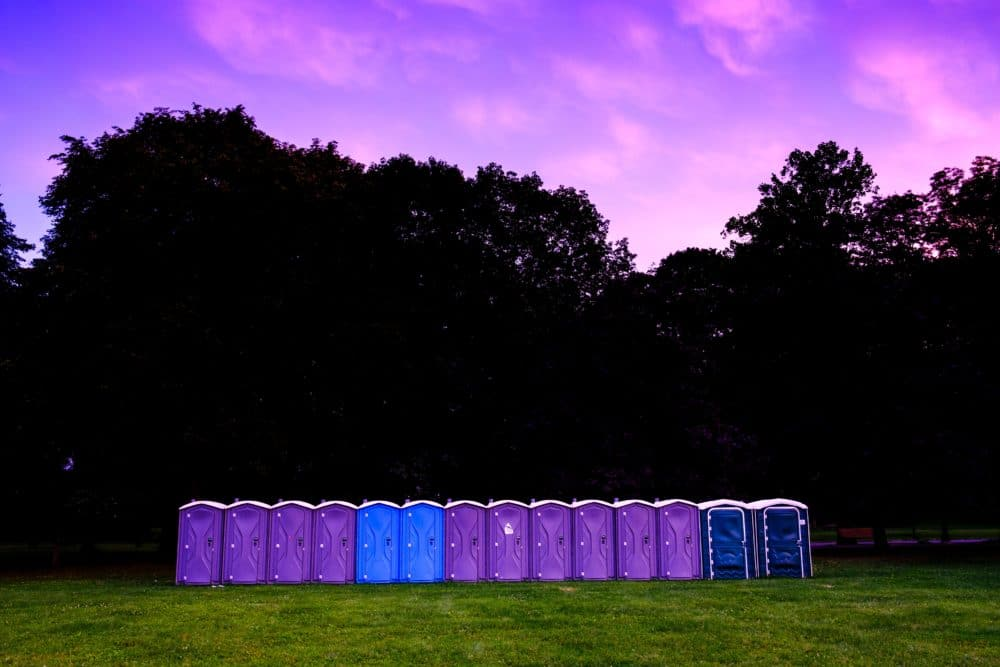 A row of portable toilets outside during sunrise.