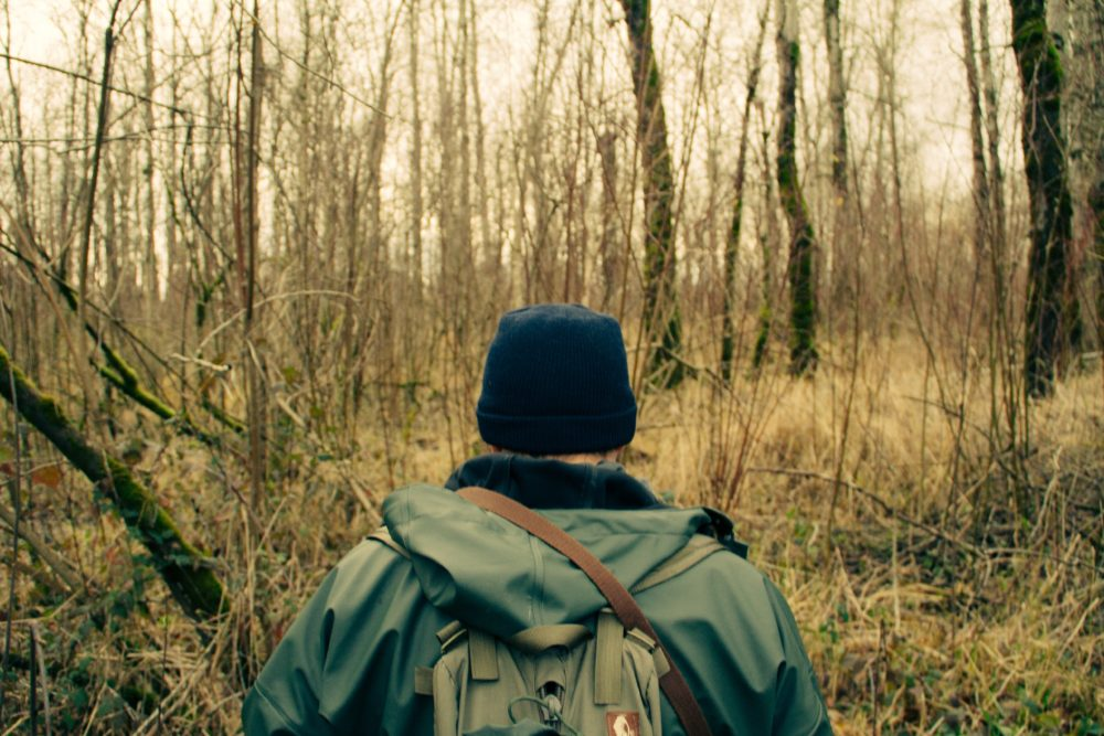 A man with a blue hat walking in the forest.