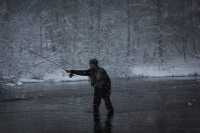 A man fishing on a lake in the snow.
